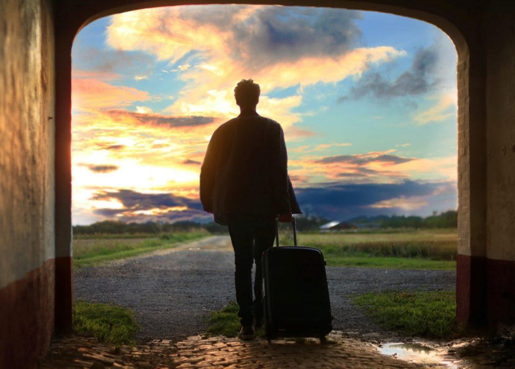 スーツケースを持つ男性の後ろ姿